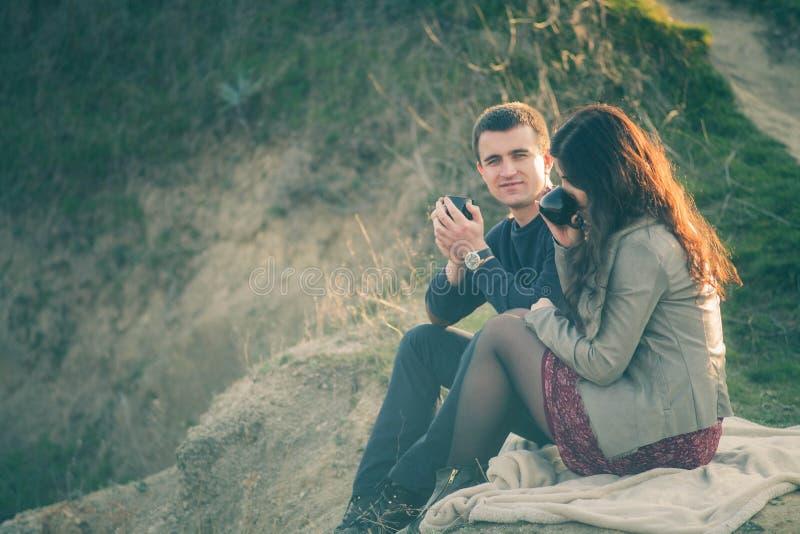 Té al aire libre de los pares jovenes cariñosos junto, de consumición feliz Un individuo con una muchacha en el lago en la puesta imagen de archivo libre de regalías