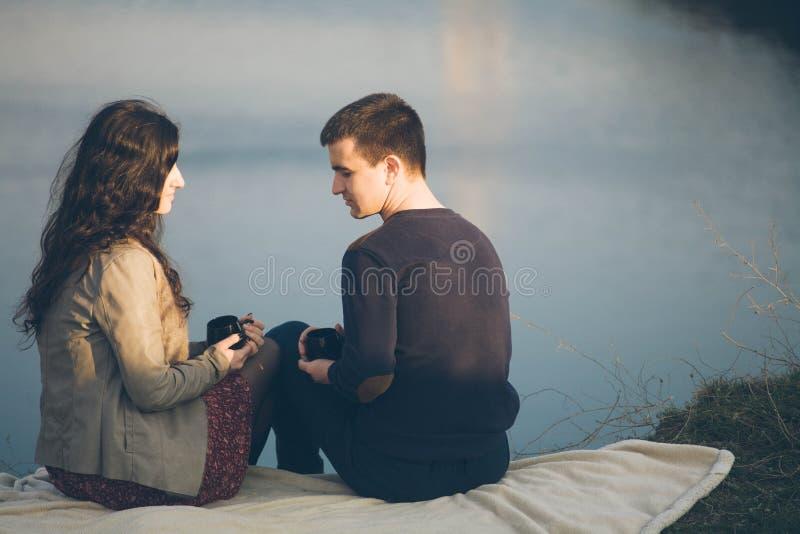 Té al aire libre de los pares jovenes cariñosos junto, de consumición feliz Un individuo con una muchacha en el lago en la puesta foto de archivo libre de regalías