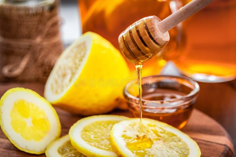 Té caliente con el limón y miel natural, buena invitación para tener vitaminas e inmunidad fuerte fotografía de archivo