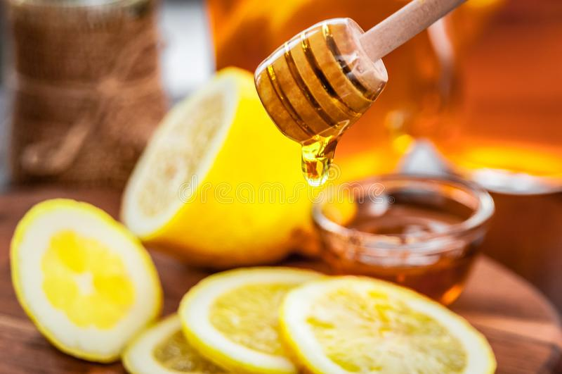 Té caliente con el limón y miel natural, buena invitación para tener vitaminas e inmunidad fuerte imagen de archivo