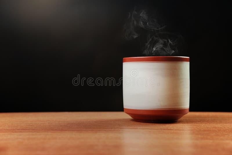 Té caliente con vapor en taza de té de cerámica foto de archivo