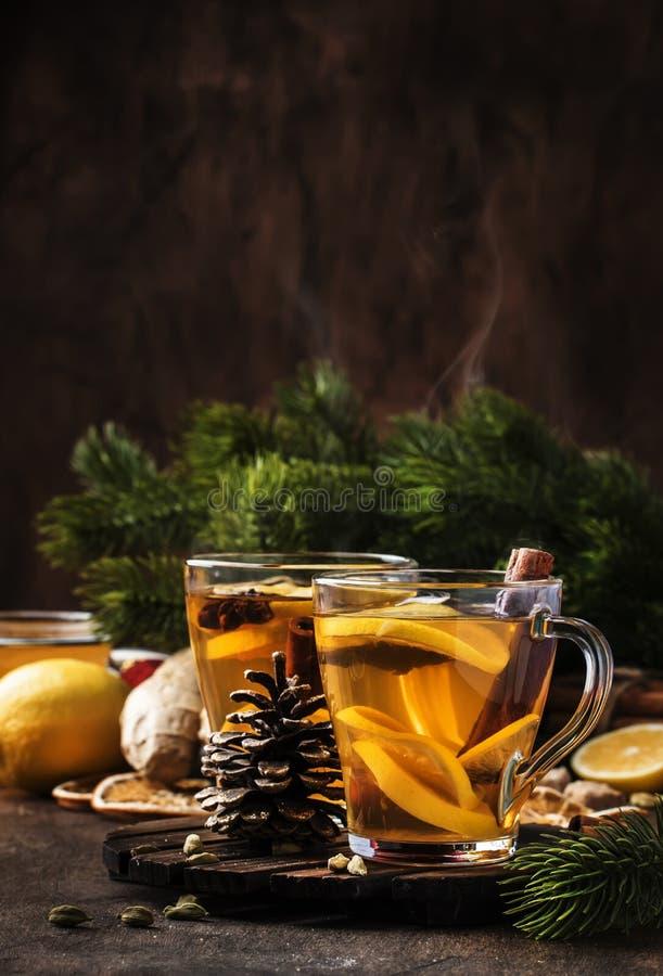 Té caliente de invierno con fruta, limón y especias en vaso de vidrio con vapor en Navidad o Año Nuevo, madera rústica foto de archivo