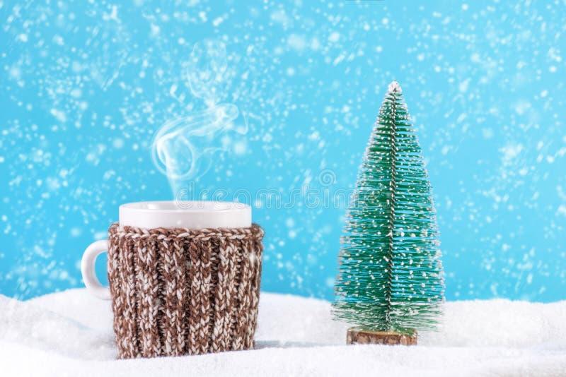 Té caliente de la bebida de la Navidad en taza con el árbol de abeto de la bufanda y de Navidad de las lanas en nieve imágenes de archivo libres de regalías