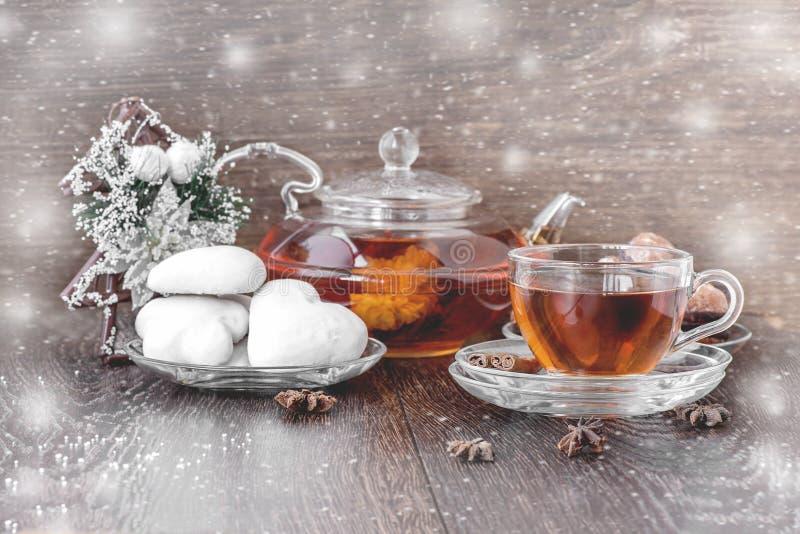Té caliente en la Navidad en la taza transparente de cristal con té, el pan de jengibre, el canela y la vainilla Postal con la ni fotos de archivo libres de regalías