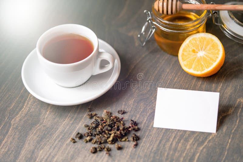 Té con el limón y la miel en la tabla rústica de madera con la tarjeta de visita en blanco foto de archivo