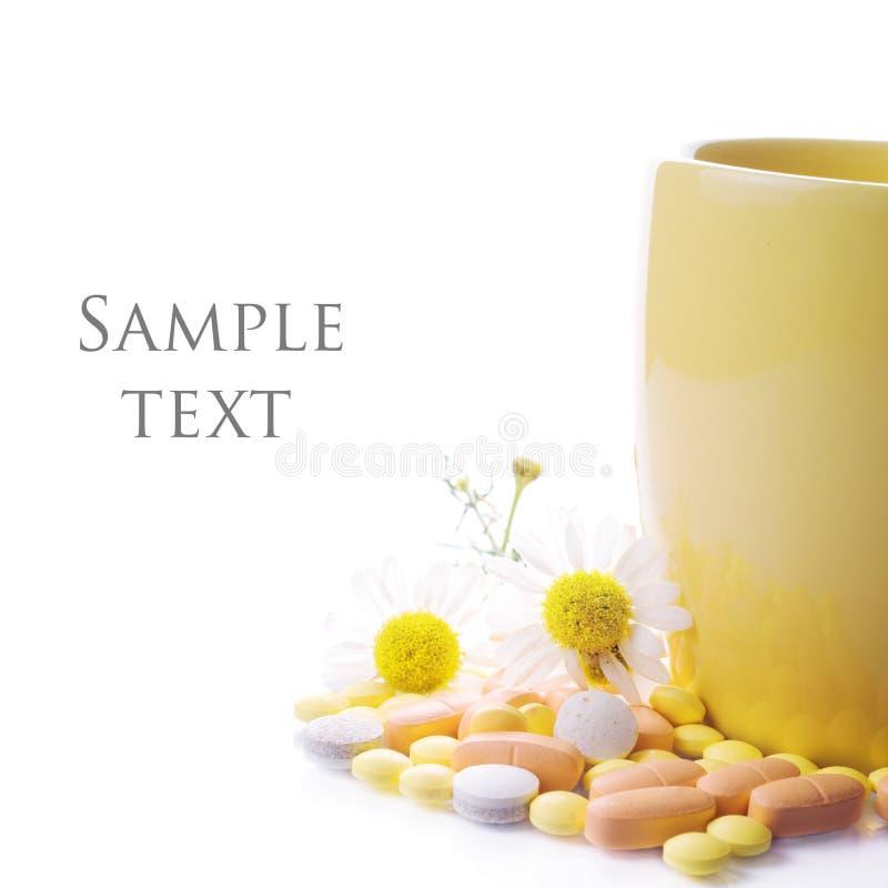 Té con la manzanilla y las píldoras imagenes de archivo