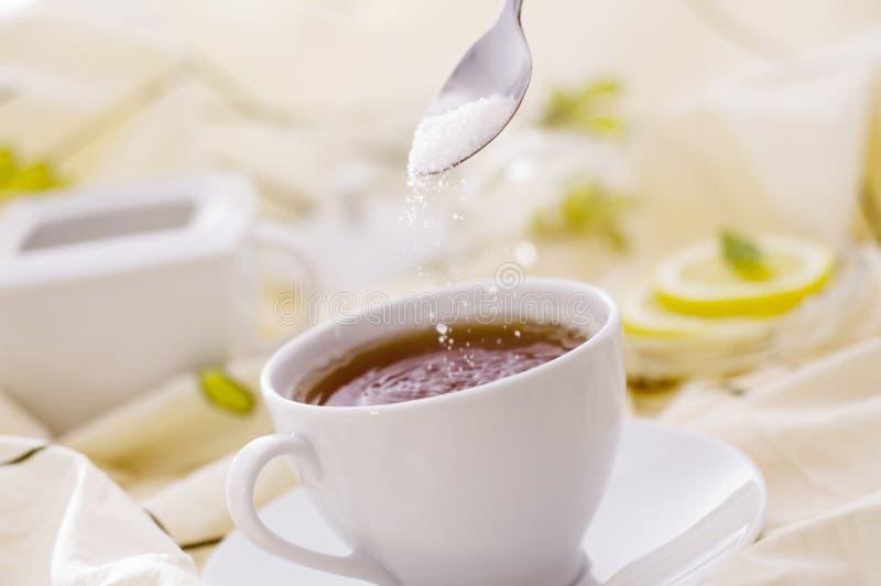 Té con la taza blanca con el azúcar foto de archivo