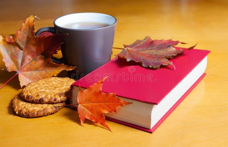 Té con las galletas, el libro y las hojas de otoño Foco selectivo fotografía de archivo libre de regalías