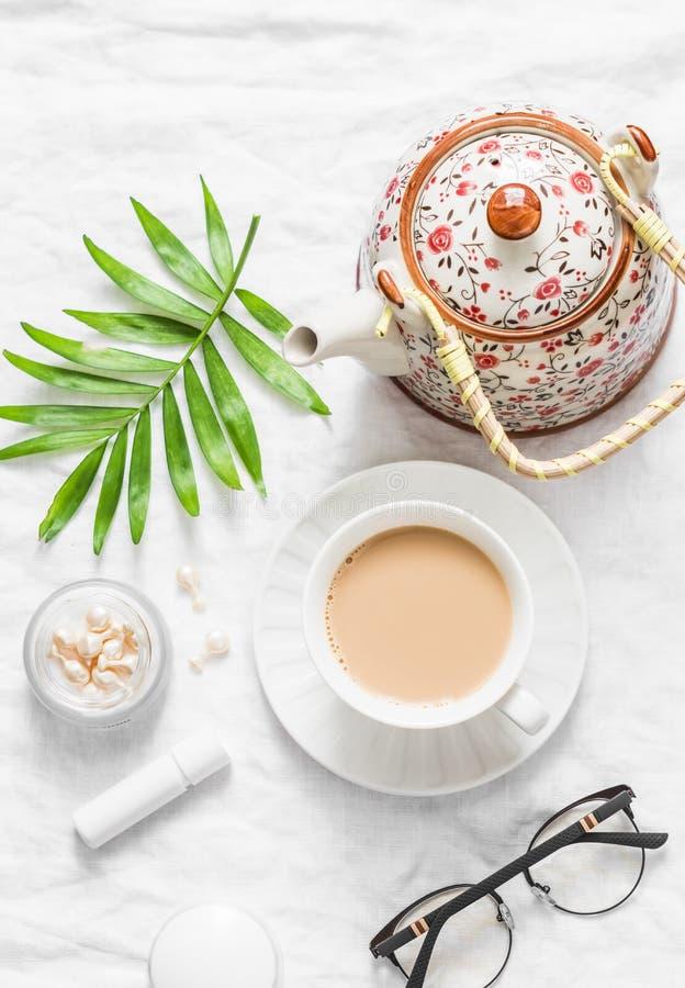 Té con leche Té de Masala, tetera, cosméticos, lápiz labial, aceite facial, vidrios, flor verde de la hoja en el fondo ligero, vi foto de archivo libre de regalías