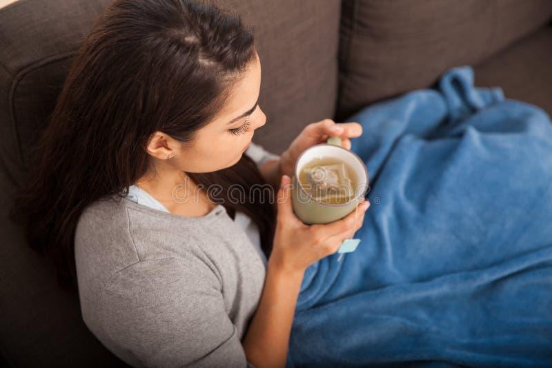 Té de consumición de la muchacha fría en casa fotografía de archivo libre de regalías