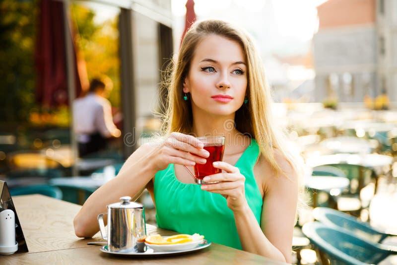 Té de consumición de la mujer hermosa en un café al aire libre imagen de archivo
