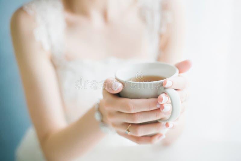Té de consumición de la novia de una taza blanca imagen de archivo