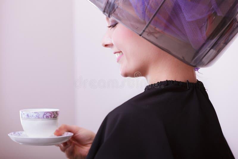 Té de consumición del café de la muchacha del peluquero. Hairdryer en salón de belleza del pelo. foto de archivo libre de regalías