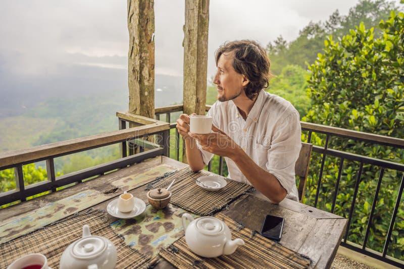 Té de consumición del hombre en un café en las montañas imagen de archivo libre de regalías