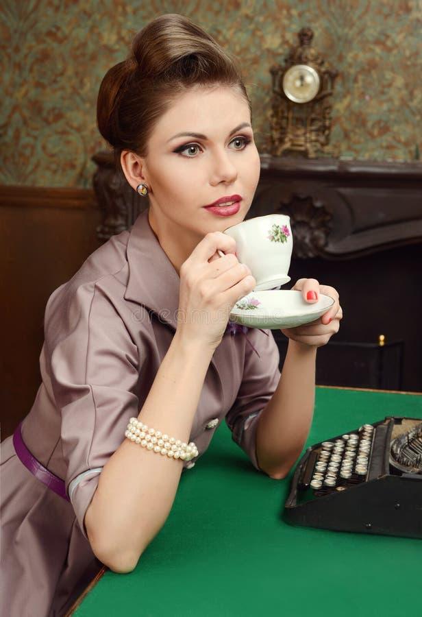 Té de consumición hermoso de la mujer joven de Pin Up en interior del vintage fotos de archivo