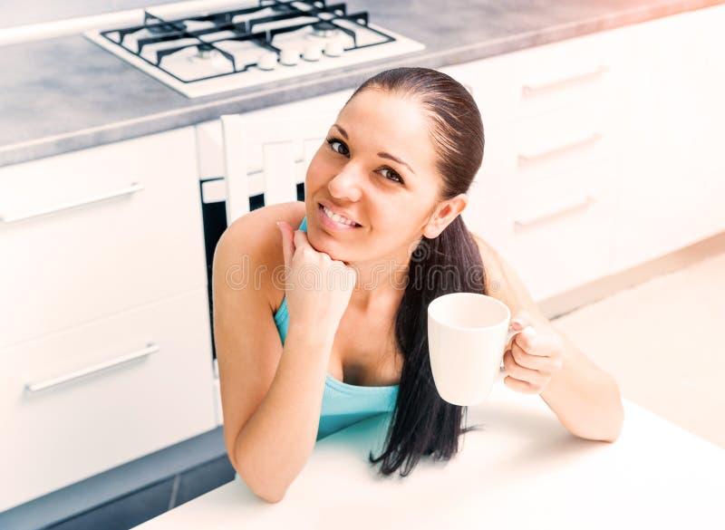 Té de consumición de la muchacha hermosa en la cocina imagen de archivo