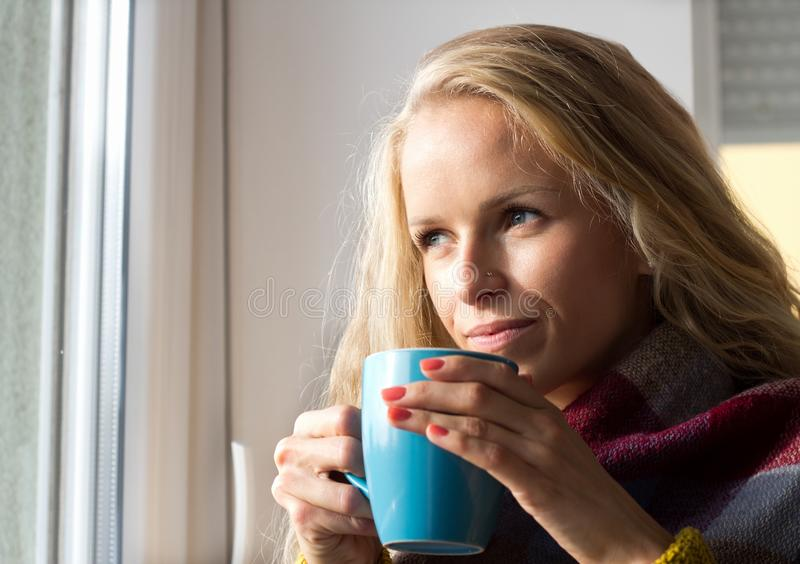 Té de consumición de la mujer al lado de la ventana en invierno fotografía de archivo