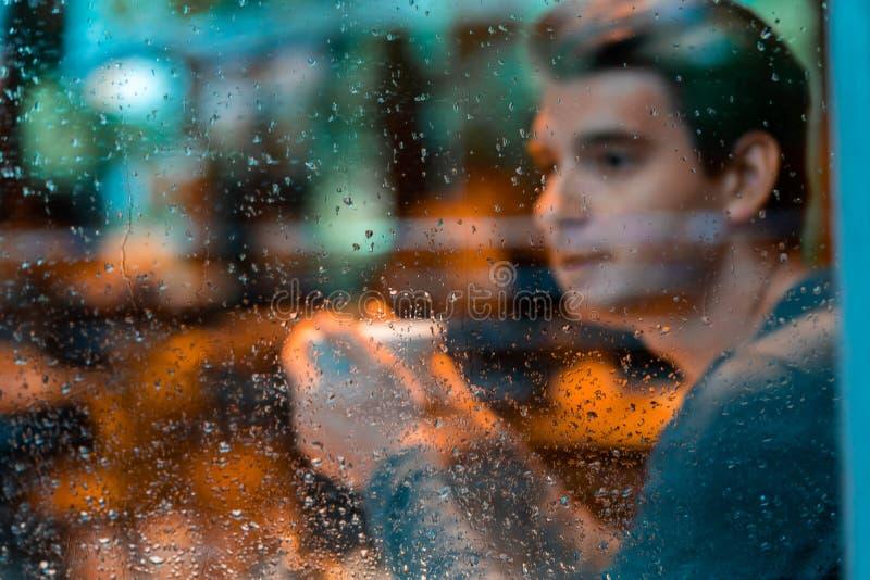 Té de consumición o café en día lluvioso y mirada del hombre hermoso a través de la ventana imagenes de archivo