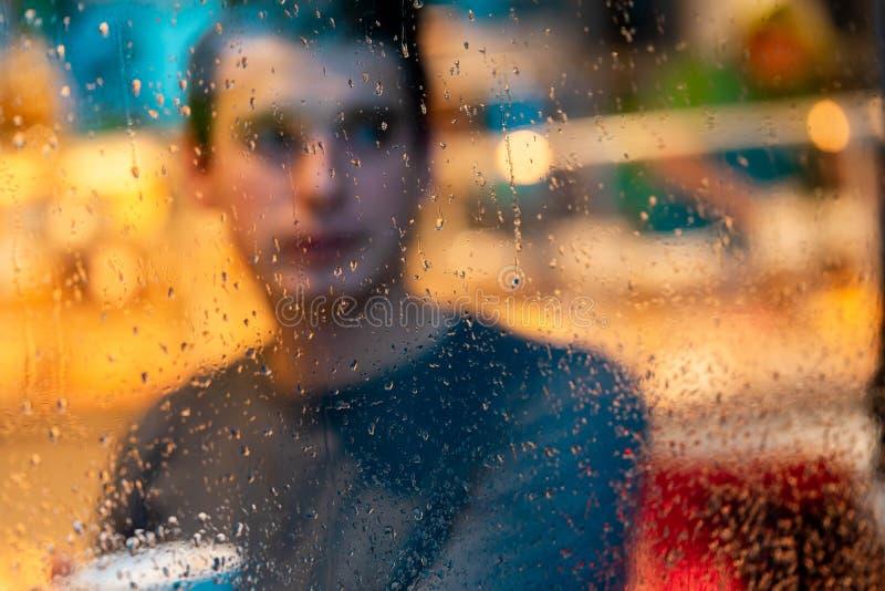 Té de consumición o café en día lluvioso y mirada del hombre hermoso a través de la ventana foto de archivo libre de regalías