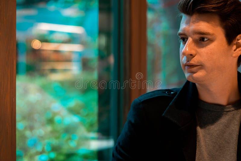Té de consumición o café en día lluvioso y mirada del hombre hermoso a través de la ventana foto de archivo