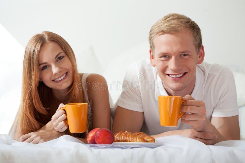 Té de consumición sonriente de los pares en cama imágenes de archivo libres de regalías