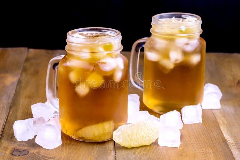 Té de hielo frío del verano con el cubo de la fruta cítrica y de hielo en cierre de madera del fondo del tarro de cristal encima  imagen de archivo