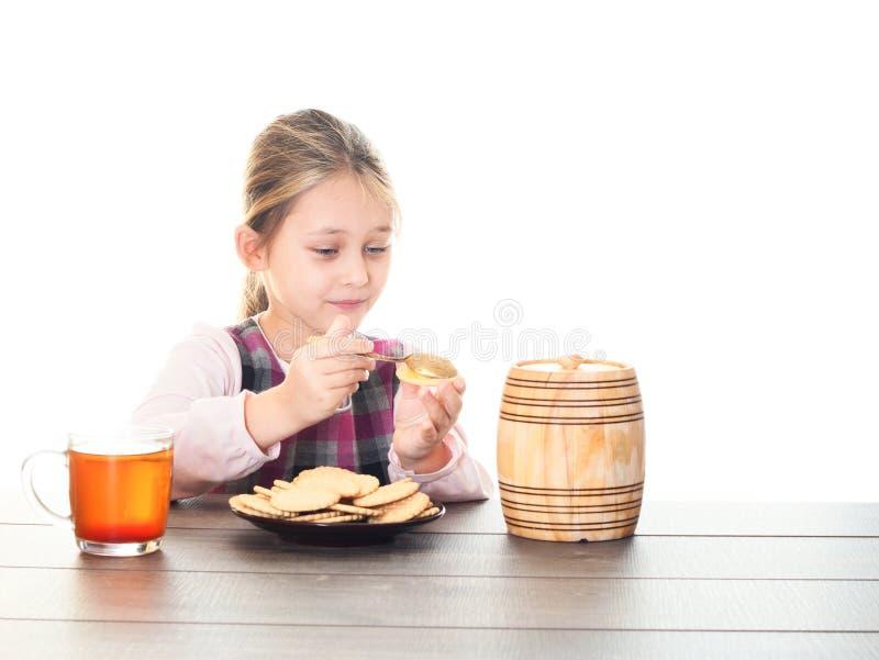 Té de la bebida del niño con las galletas y la miel fotos de archivo