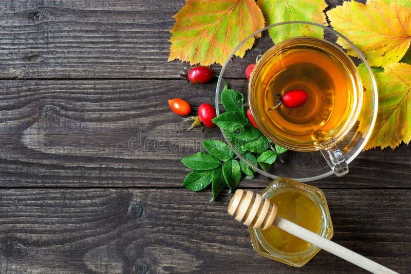 Té de la cadera de Rose con la miel en taza transparente con las hojas de otoño fotos de archivo