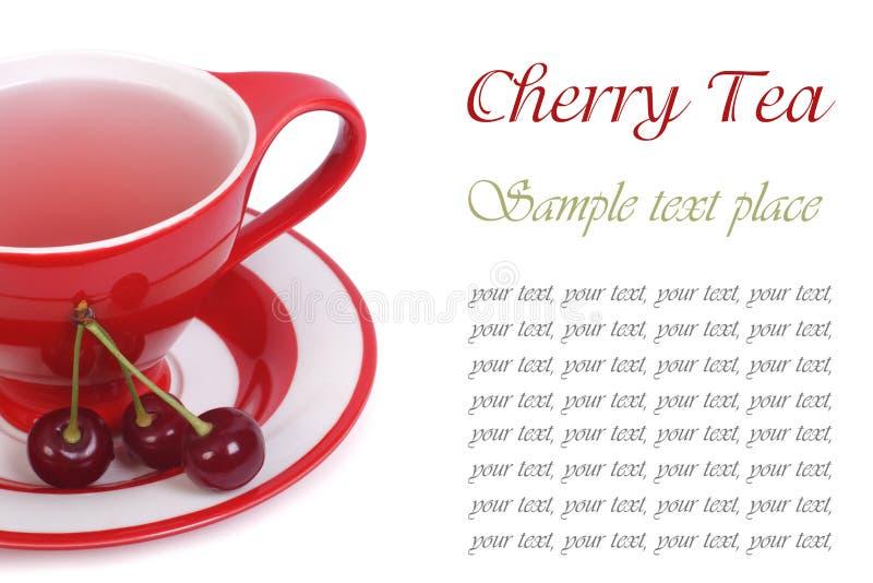 Té de la fruta con la cereza en una taza roja aislada en blanco fotos de archivo