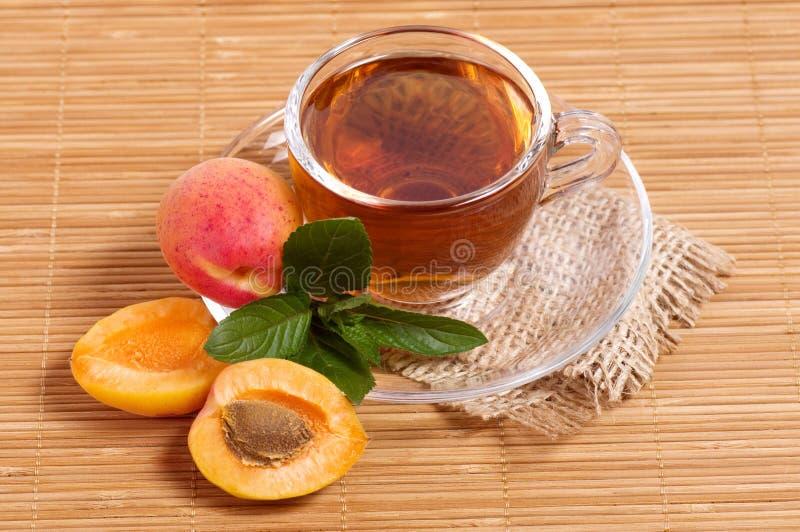 Té de la fruta en taza con el albaricoque imagen de archivo