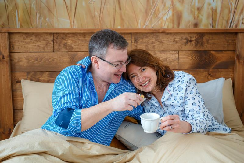Té de la mañana El marido trajo su café del té de la esposa a la cama foto de archivo