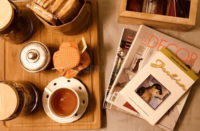 Té de la tabla de la mañana de Italia con las revistas y el libro imagenes de archivo