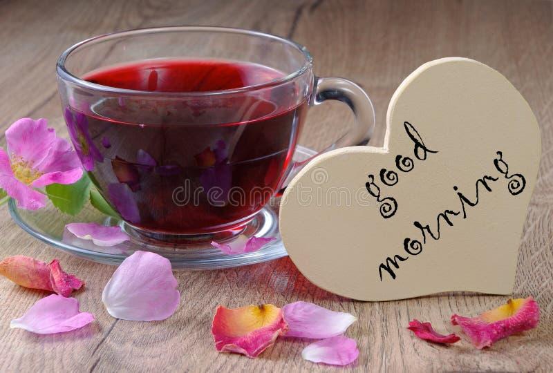 Té de las vitaminas Buenos días té del hibisco y rosas salvajes en una tabla de madera Símbolo del corazón del amor imágenes de archivo libres de regalías