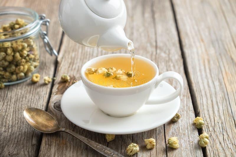 Té de manzanilla sano vertido en la taza blanca Tetera y cuchara, tarro de hierbas de la margarita foto de archivo