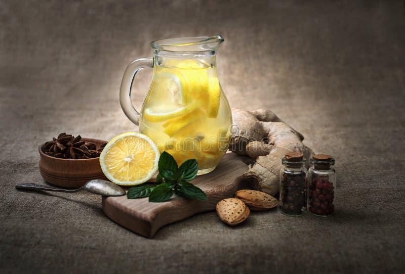 Té del jengibre con el limón, la raíz del jengibre y la menta en fondo rústico imagen de archivo