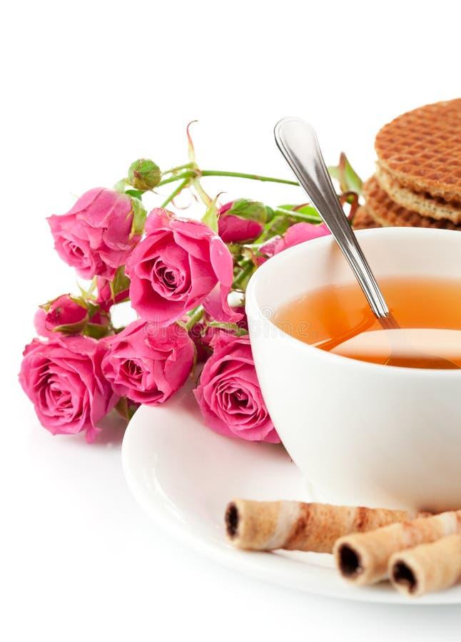 Té en taza con las galletas y las rosas del ramo imagen de archivo