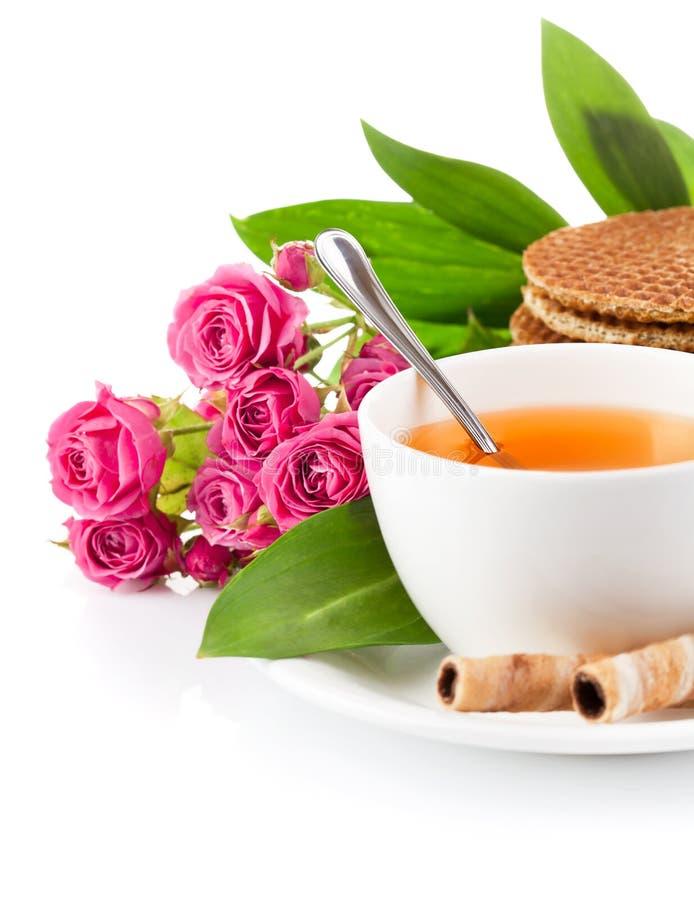 Té en taza con las galletas y las rosas del ramo foto de archivo
