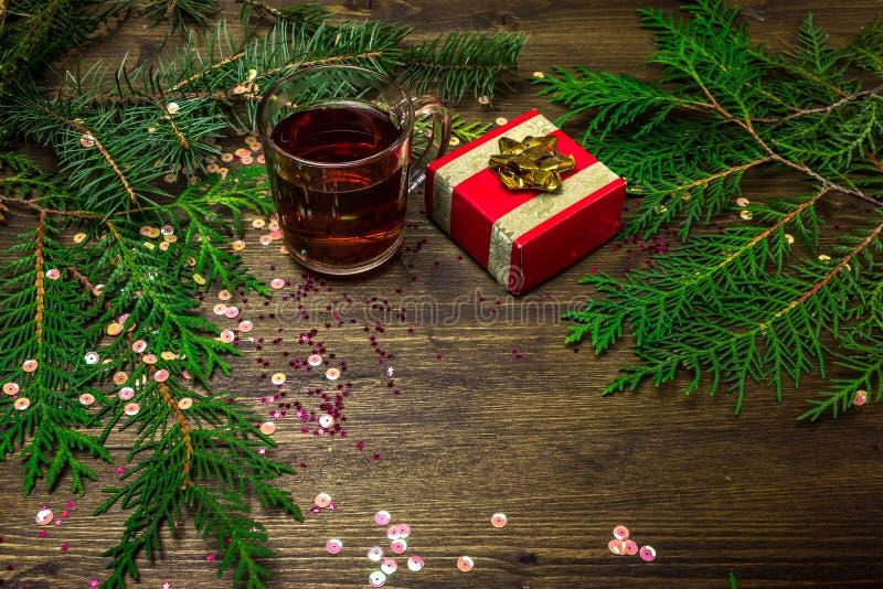 Té en una taza de cristal, ramas spruce, la Navidad foto de archivo
