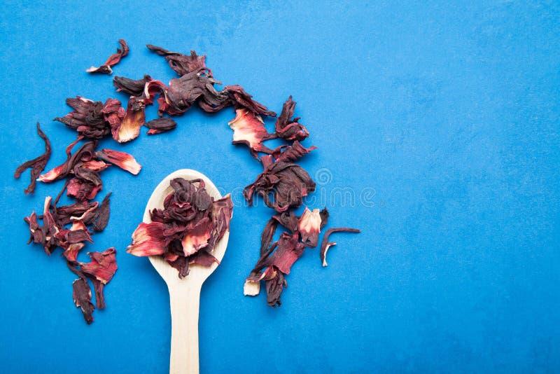 Té exótico delicioso hecho de hibisco seco en un fondo azul Copie el espacio foto de archivo