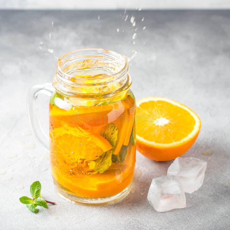 Té frío con la naranja, la menta y el hielo, bebida dulce del verano, limonada de restauración, cóctel jugoso Espray, chapoteo imagen de archivo libre de regalías