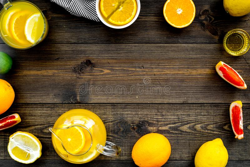 Té fragante caliente con las frutas La taza de té y la tetera cerca de frutas cítricas en la opinión superior del fondo de madera imagenes de archivo