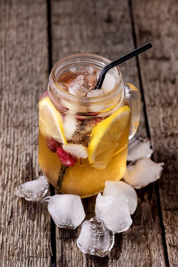 Té helado frío con la rebanada de limón y de frambuesa en Mason Jar en el té frío sabroso de la vertical rústica de madera del fo foto de archivo libre de regalías