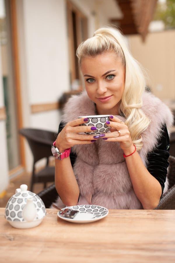 Té hermoso de la bebida de la mujer joven en terace de la barra en otoño temprano fotografía de archivo