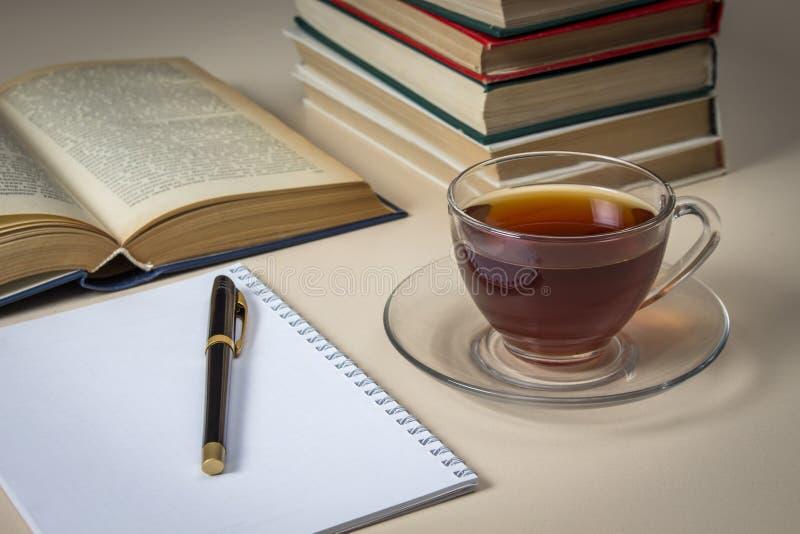 Té, libros y cuaderno en la tabla blanca imagen de archivo