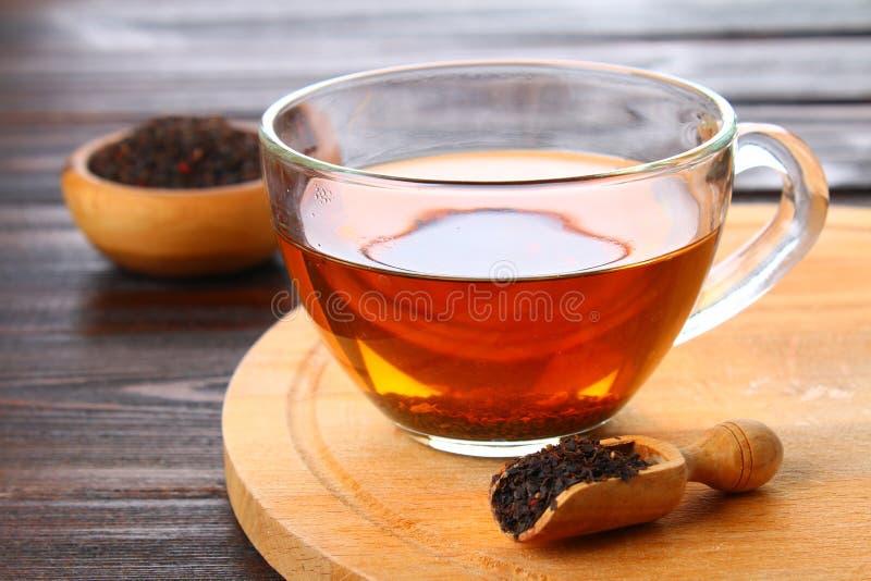 Té negro caliente en una taza de cristal y té seco en una tabla de madera imagenes de archivo