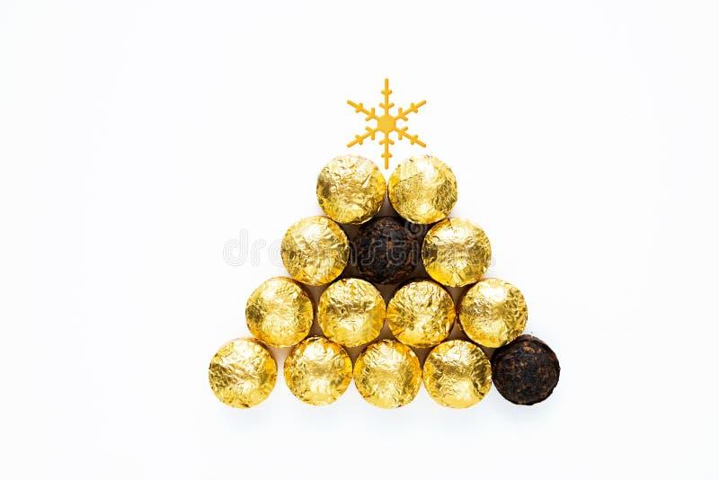 Té negro chino seco PU-erh moldeado en envoltura y sin ella, en forma de árbol de Navidad sobre fondo blanco imagen de archivo libre de regalías
