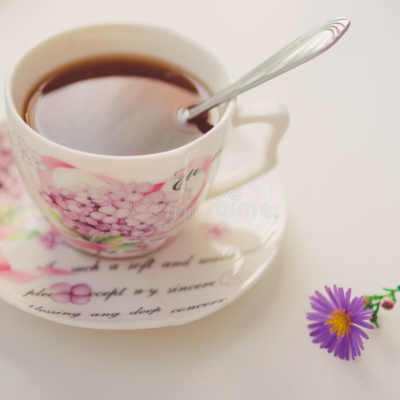 Té negro con cuchara en una elegante taza de porcelana en la mesa blanca Crisantemo de flor violeta Delicada cerca foto de archivo