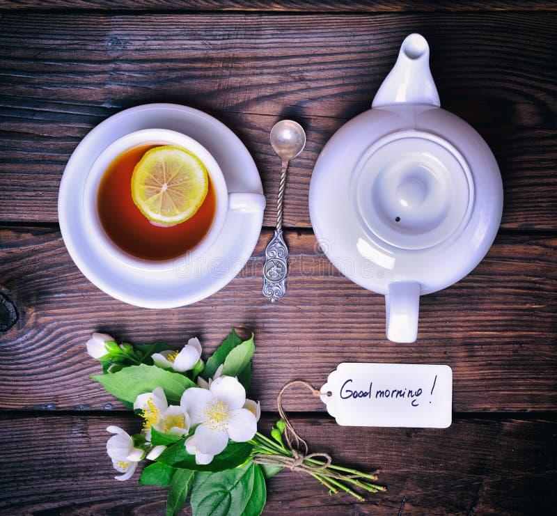 Té negro con el limón y el pote blanco del té foto de archivo