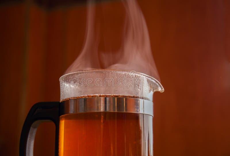 Té negro en el cocido al vapor al vapor de cristal de la caldera fotografía de archivo libre de regalías
