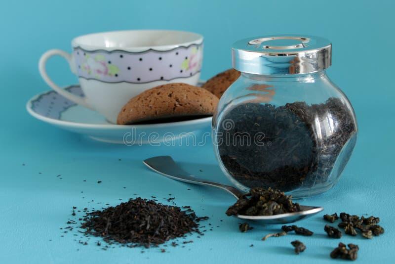Té negro secado en la cuchara del pote en la tabla azul y una galleta fotos de archivo